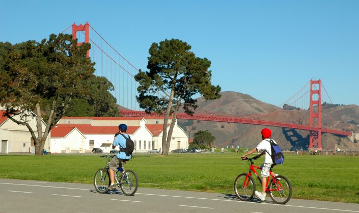 bicyclists riding on a path with the Golden Gate Bridge in the background